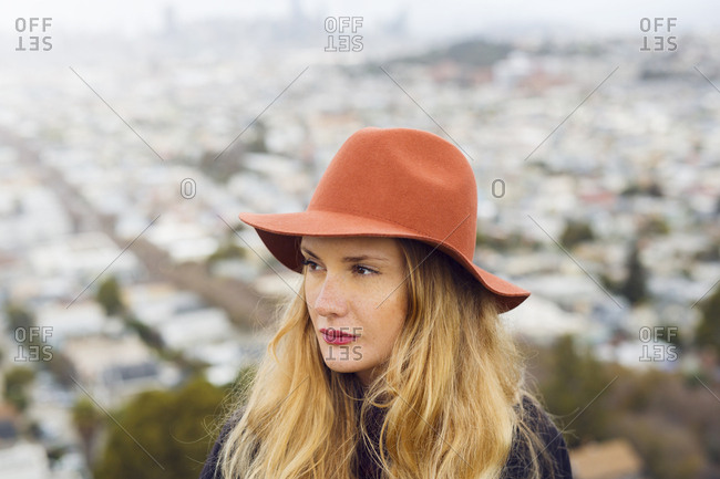 Portrait of young woman wearing red hat in front of cityscape