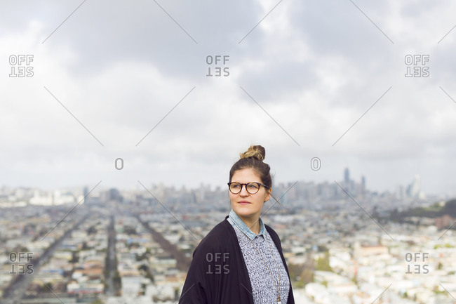 Portrait of young woman in front of cityscape