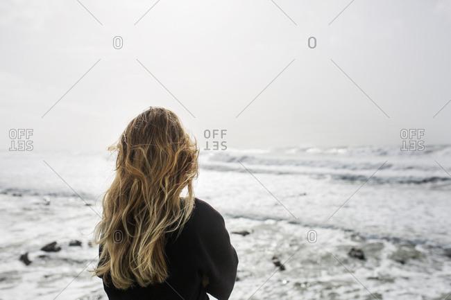 Rear view of blonde woman looking at ocean
