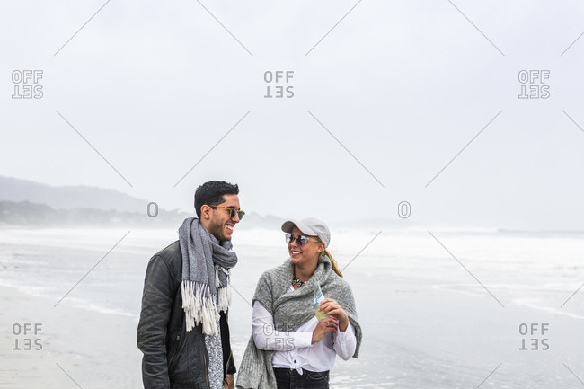 Young couple walking on beach and talking