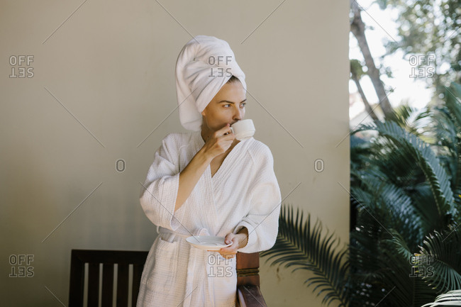 Portrait of a beautiful young woman with glasses in the hotel in a bathrobe and a towel, drinking coffee on the balcony