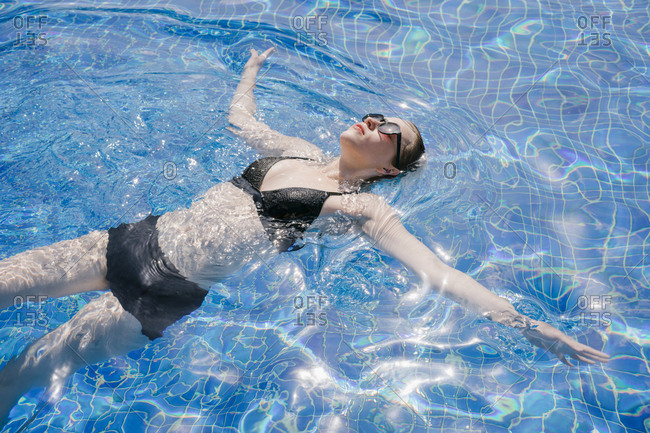Portrait of a beautiful young woman swimming in the water pool, resting in the hotel pool.
