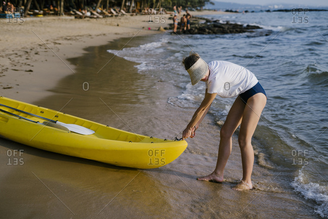 Portrait of a beautiful young woman drags a kayak into the sea.