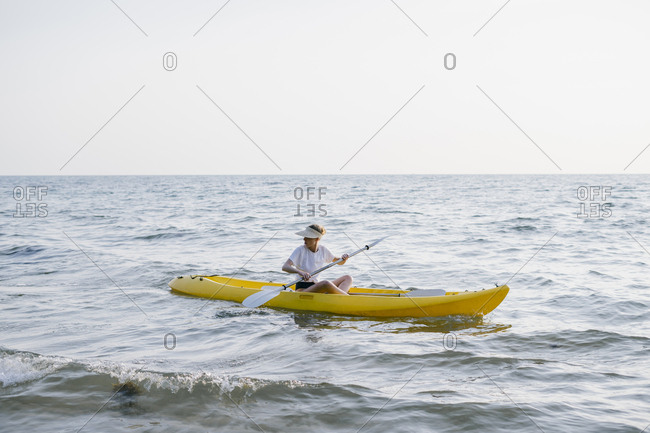 Portrait of a beautiful young woman is kayaking on the sea.
