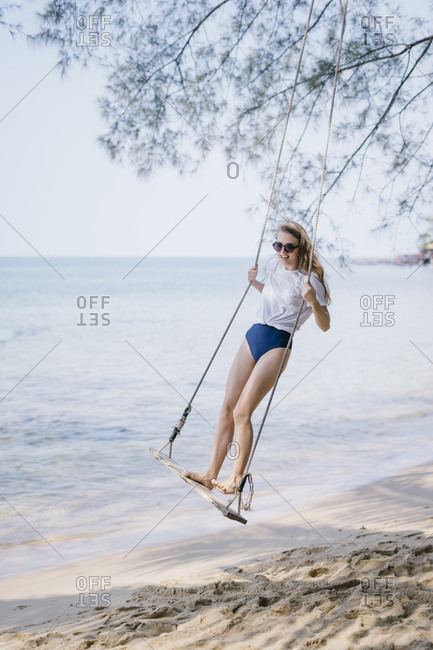 Portrait of a beautiful young woman swinging on a beach swing.