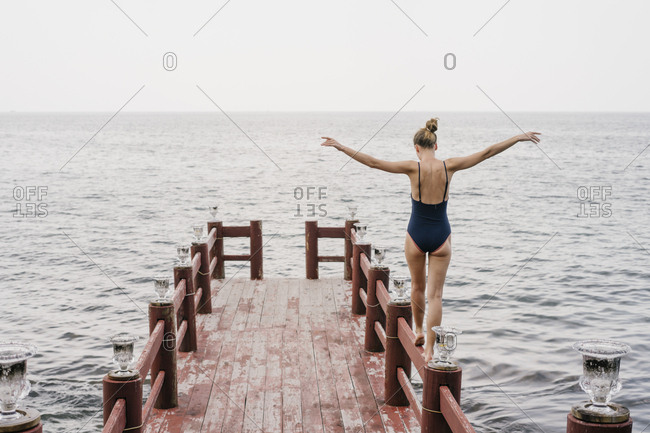 Portrait of a beautiful young woman in a bathing suit walking on the pier