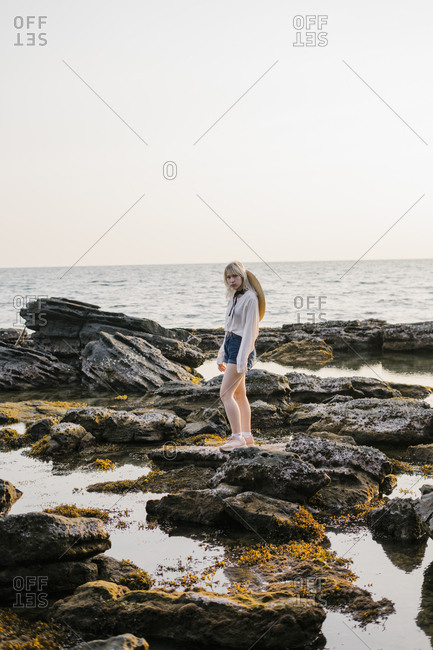 Portrait of a beautiful young woman walking on the rocks by the sea in Vietnam.