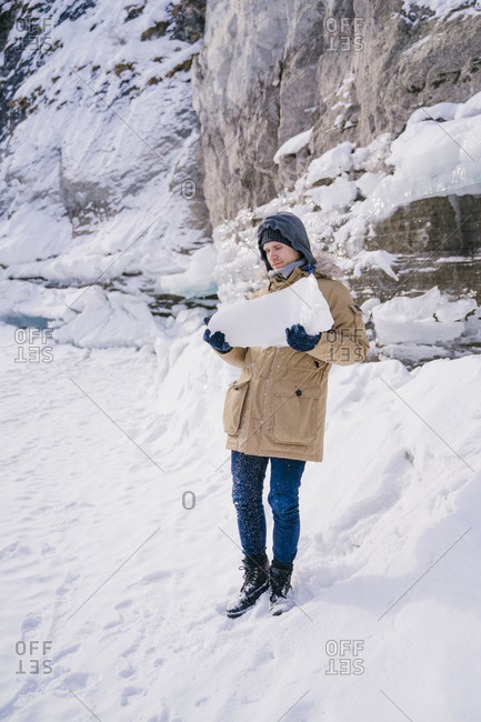 A young man holds a piece of ice on a frozen lake on a journey.