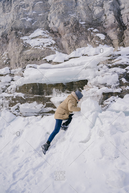 A young man climbs on an ice floe on a frozen lake on a journey.