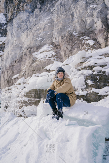 A young man sits on an ice floe and looks forward to a frozen lake on a journey.