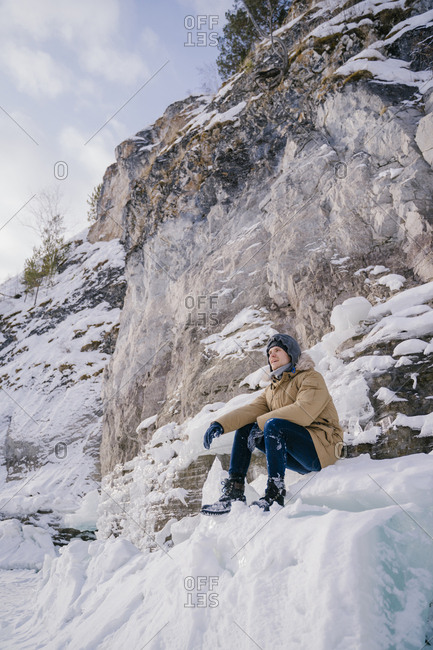 A young man sitting on an ice floe and looking forward to the background of rocks in the ice