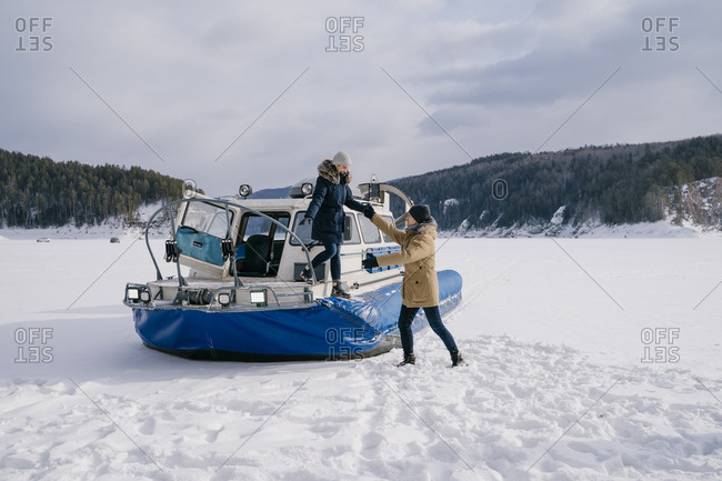 Couple in love on a walk in the winter on the lake drive a car on an air cushion on the ice