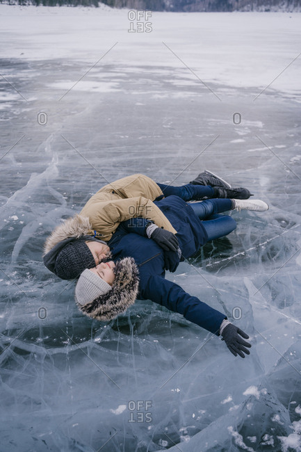 A man and a woman are lying on the ice of a frozen lake, looking at each other.