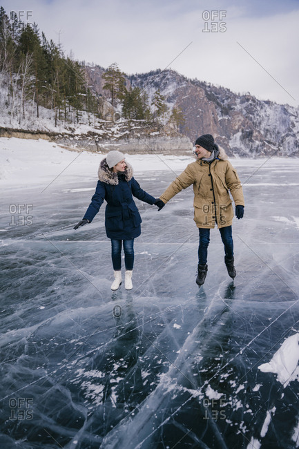 Beautiful young couple skating on the ice of the river.