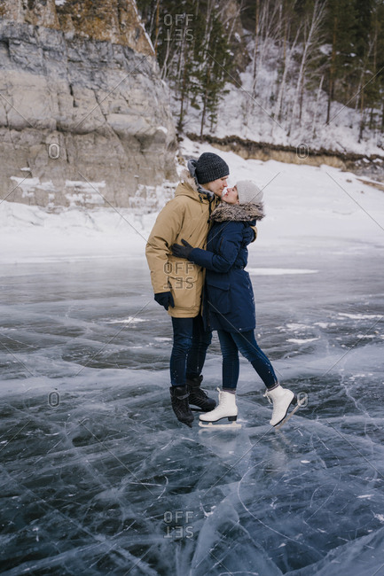 Man and woman kiss, skating on the ice of a frozen lake and look ahead.