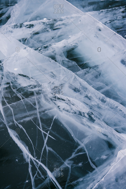 Beautiful large cracks on the ice of a frozen lake in winter.