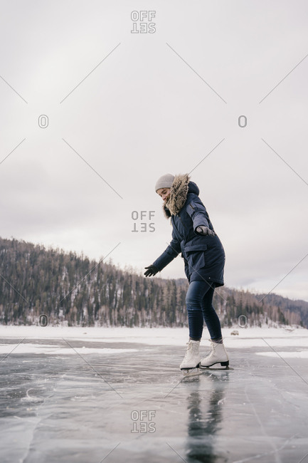Young beautiful girl skates on the ice of a frozen lake in winter.