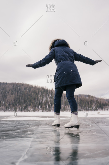 Young beautiful woman skates on the ice of a frozen lake in winter.