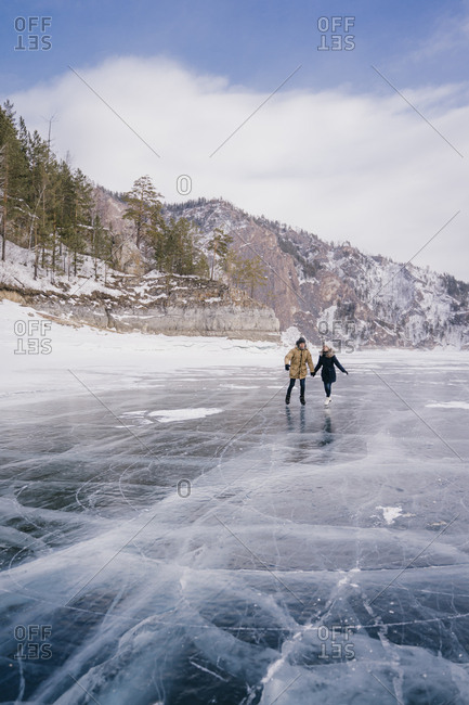 A man and a woman go ice-skating on the ice of a frozen lake and look ahead.
