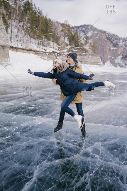The guy with the girl are skating and holding hands against the backdrop of the mountains.