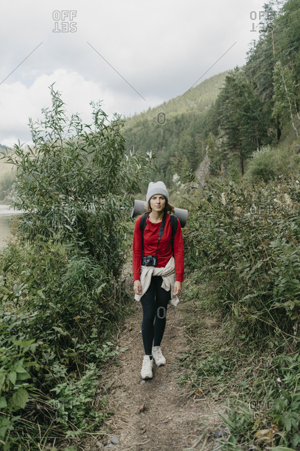 Beautiful young woman traveler with backpack and camera walking in the mountains along the river in nature