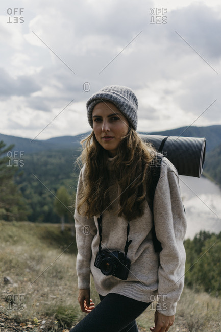 Beautiful young woman with backpack and film walks along a path in the forest