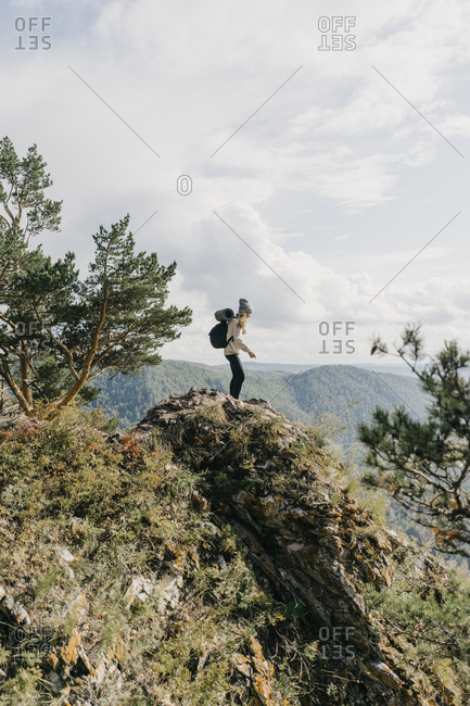 Beautiful young woman with backpack and film camera walking along the path in the forest.