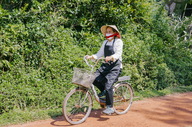 Phu Quoc, Vietnam - January 18, 2019: Vietnamese woman in a hat riding a bike with a basket to work at the hotel.