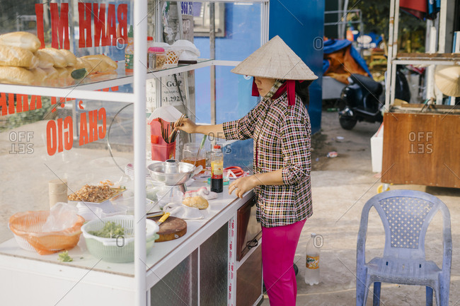 Phu Quoc, Vietnam - January 19, 2019: Vietnamese woman in hat prepares street food sandwich bahn me with ham, pate and vegetables.