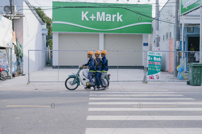 Phu Quoc, Vietnam - January 19, 2019: Vietnamese builders workers riding on a scooter motorcycle.