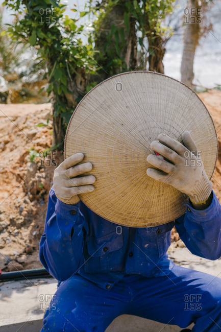 Vietnamese Builder covers his face with a straw hat.