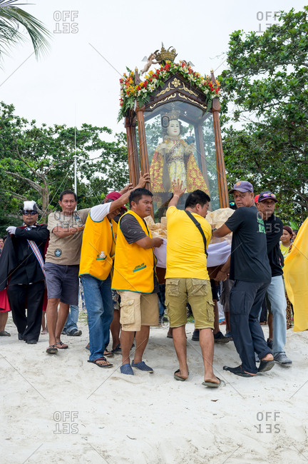 January 26, 2019: People carrying the image of The Santo Nino on the beach. Panglao Island, Bohol, Philippines