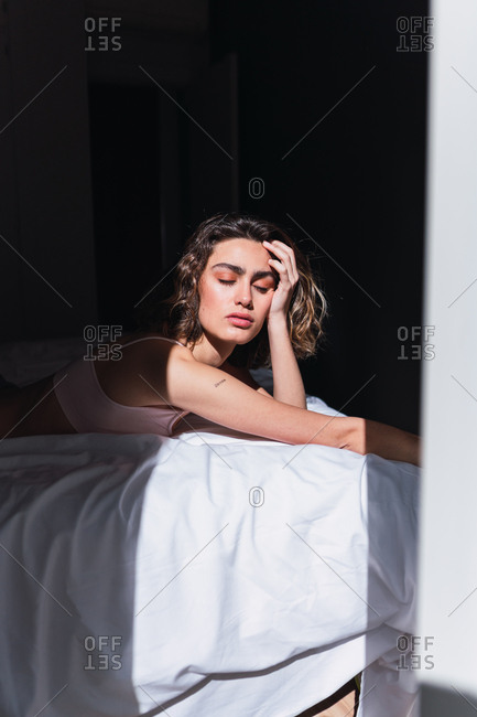 Side view of lovely charming lady with closed eyes illuminated by sun resting on bed in bedroom