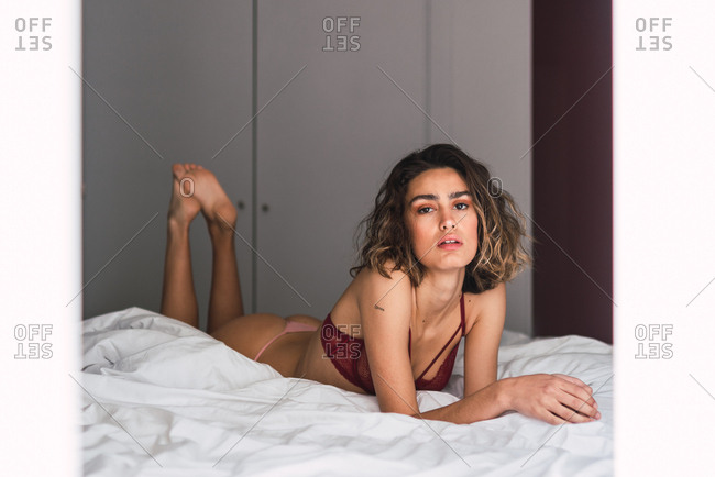 Lovely charming slim lady looking at camera and lying on bed under duvet in bedroom