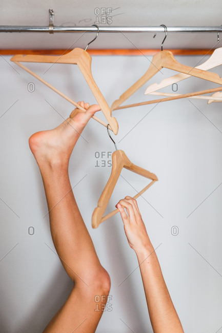 Crop hand and leg of woman touching hanger in empty wardrobe