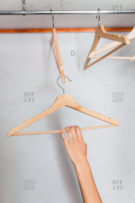 Crop hand of woman holding hanger in empty wardrobe