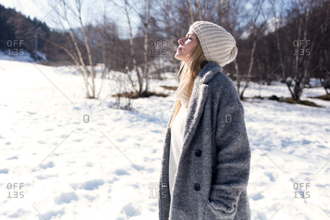 Shot of beautiful young woman breathing fresh air over winter background.