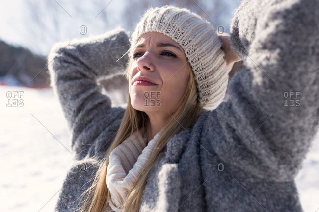 Shot of relaxing young woman breathing fresh air while putting arms on head over winter background.