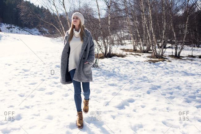 Shot of pretty young woman walking through snow while breathing fresh air over winter background.