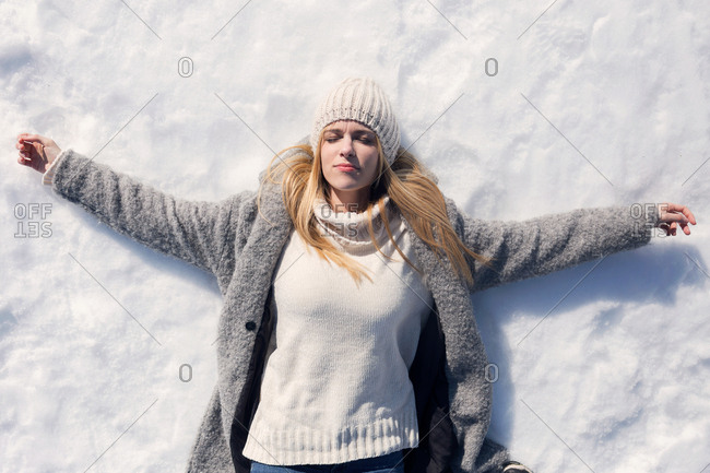 Shot of beautiful young woman with open arms lying in the snow over winter background.