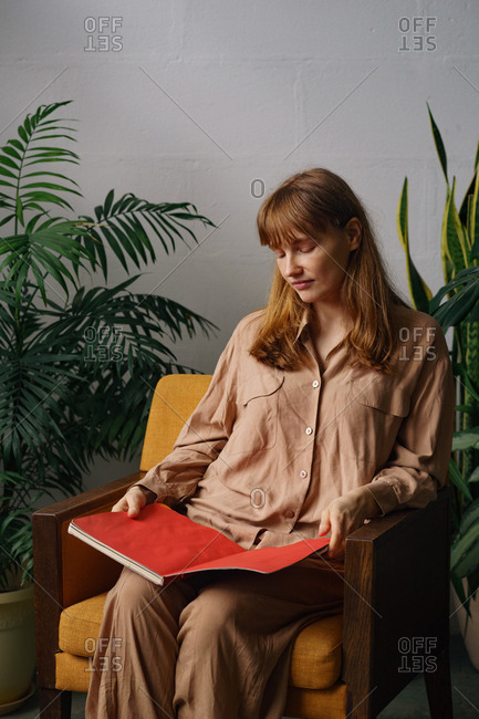 Portrait of a model with ginger hair and freckles dressed in beige oversized clothes reading in a room full of home plants