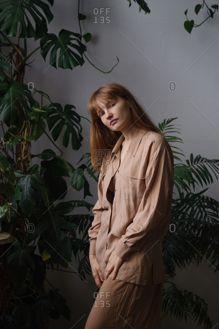 Portrait of a model with ginger hair and freckles dressed in beige oversized clothes in a room full of home plants