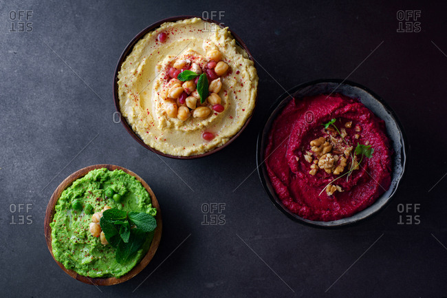 Creamy chickpea hummus, green pea hummus and spicy roasted beetroot dip