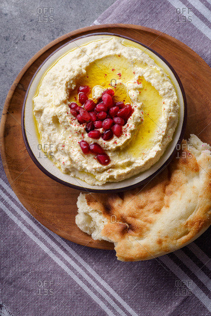 Creamy chickpea hummus with pomegranate seeds and olive oil