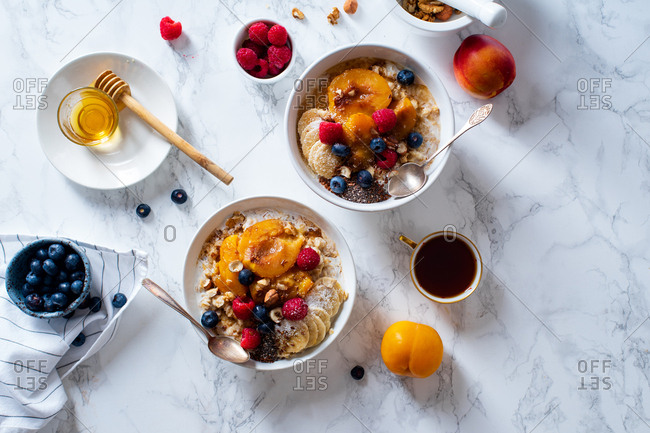 Top view of oatmeal porridge with fruits and berries on marble table