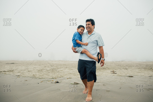 Smiling Father Carries Smiling Son At Foggy Beach