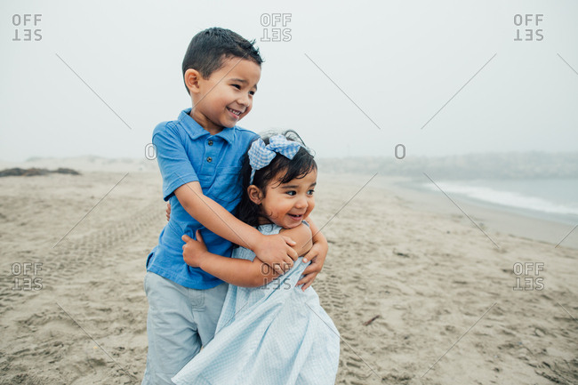 Young Siblings Smile And Embrace At Beach Looking Toward The Waves