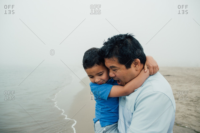 Father Holds Son Next To The Water At Foggy Beach