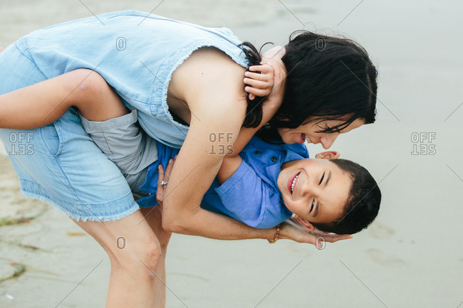Laughter As Mother Dips Young Son While At The Beach