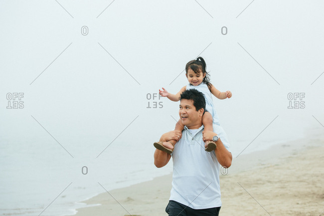 Father Carries Toddler Daughter On His Shoulders At Foggy Beach